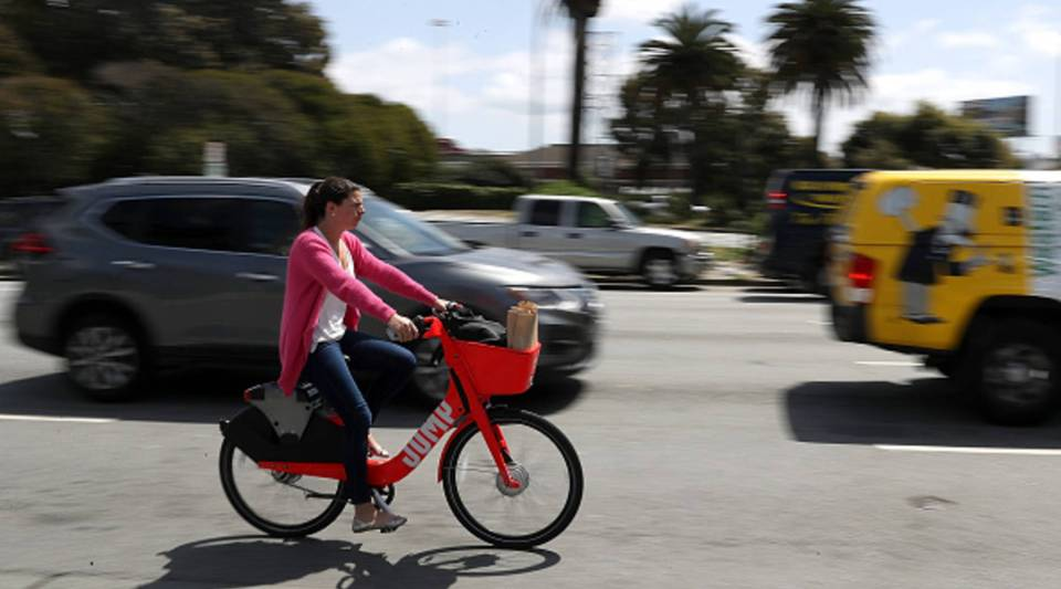A cyclist rides a JUMP bike on April 12, 2018 in San Francisco, California. Uber acquired the bike share company in April.