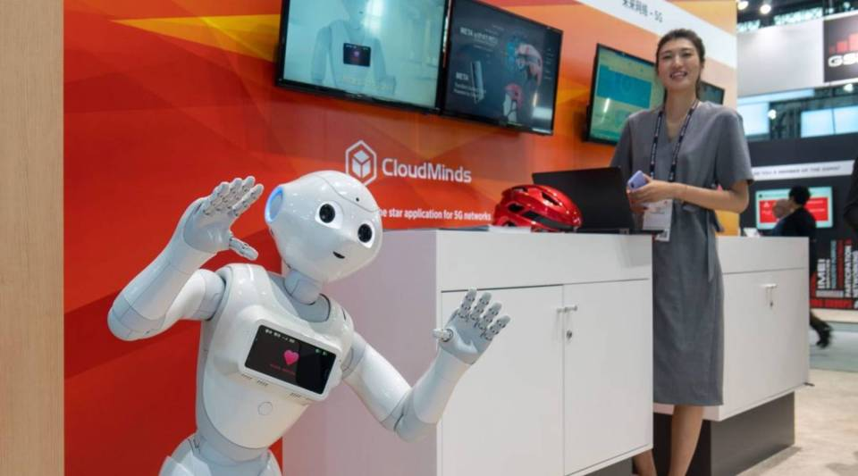 An AI robot (L) by CloudMinds is seen during the Mobile World Conference in Shanghai on June 27, 2018.