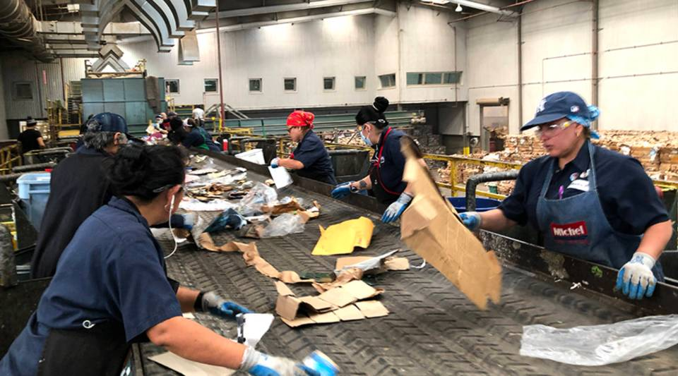 Workers sort contaminated and recyclable materials at the Puente Hills Materials Recovery Facility.