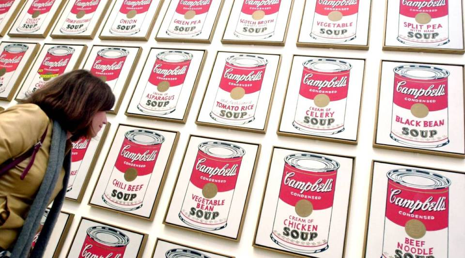 "A visitor looks at American artist Andy Warhol's ""Campbell's Soup Cans"" at the Tate Modern — a modern art gallery — in London."