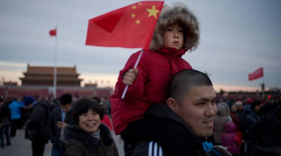 This file picture taken on March 5, 2017 shows a child holding a national flag as he sits on the shoulders of a man after the flag raising ceremony on Tiananmen Square, before the opening of the National People's Congress in Beijing. China appears poised to scrap its two-child policy, with a state-run newspaper on Aug. 27 citing a draft civil code that would overhaul decades of controversial family planning rules.