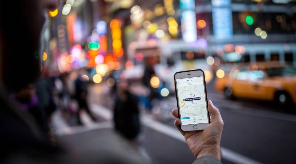 A person uses the Uber app on his iPhone in Times Square in New York City.