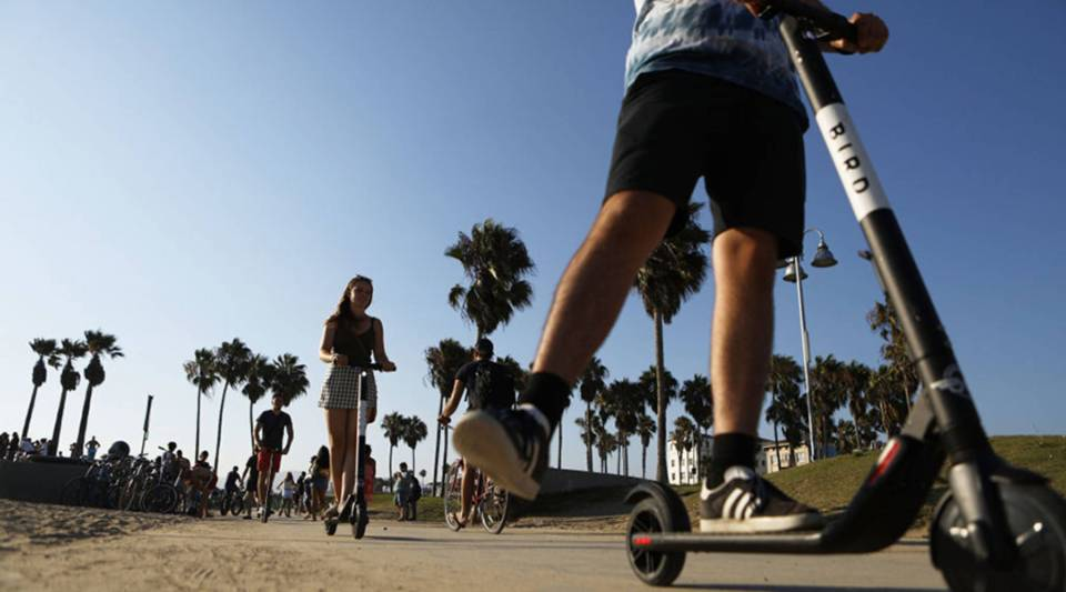 People ride Bird electric scooters along Venice Beach in August in Los Angeles.