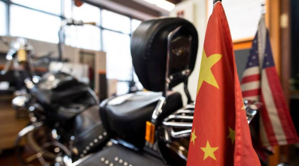 Chinese and US flags are seen on a Harley-Davidson motorcycle in the maintenance room of a dealership in Shanghai on August 24, 2018. - From Harley-Davidson motorcycles and US bourbon to Chinese parts and machinery, the world's two largest economies have exchanged punitive tariffs that slice through a wide swath of products.