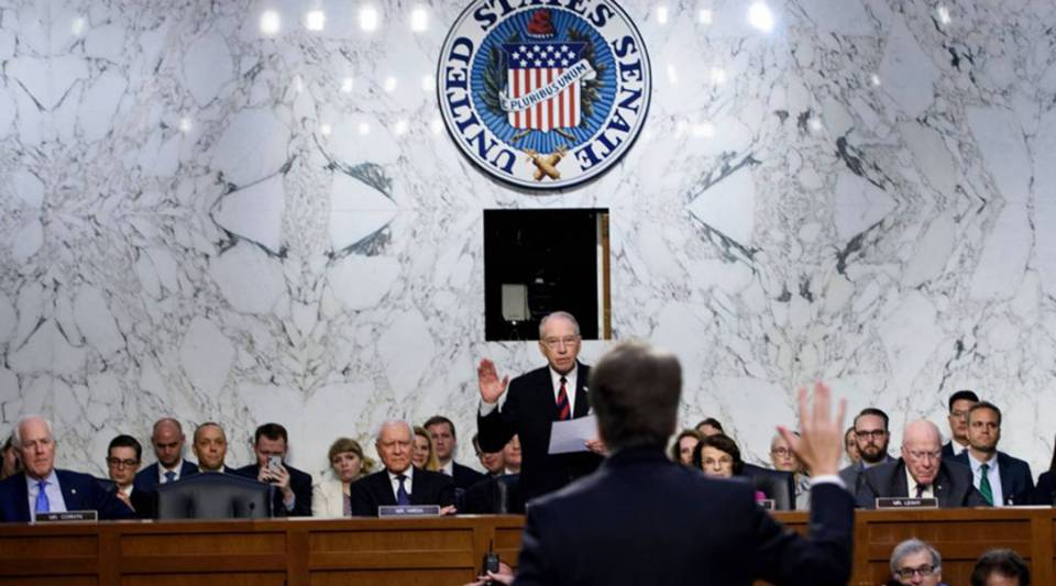Judge Brett Kavanaugh is sworn in by Chuck Grassley, rear, the chairman of the Senate Judiciary Committee, during his confirmation hearing to be an associate justice on the U.S. Supreme Court on Sept. 4.