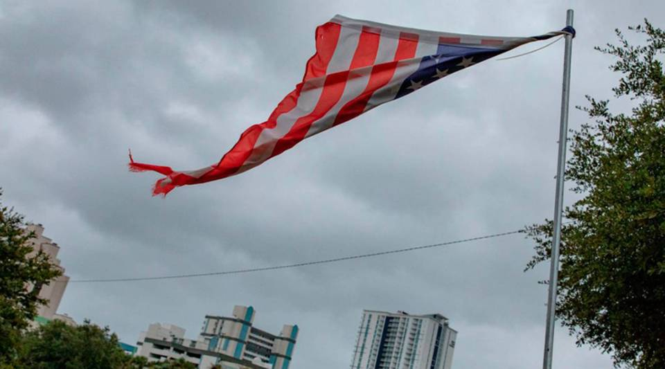 A tattered U.S. flag flies as the outer bands of Hurricane Florence make landfall Friday in Myrtle Beach, South Carolina.