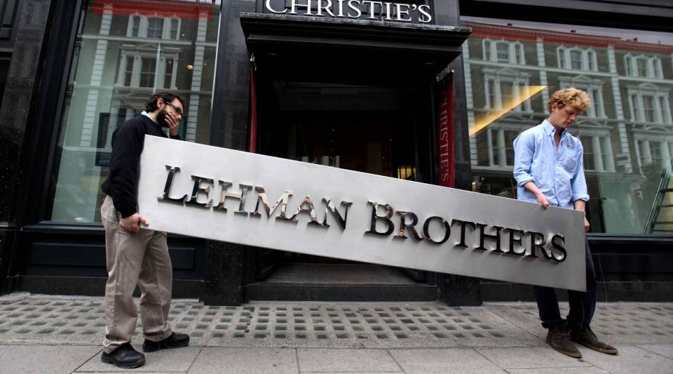 Two employees of Christie's auction house manoeuvre the Lehman Brothers corporate logo on Sept. 24, 2010 in London, England.