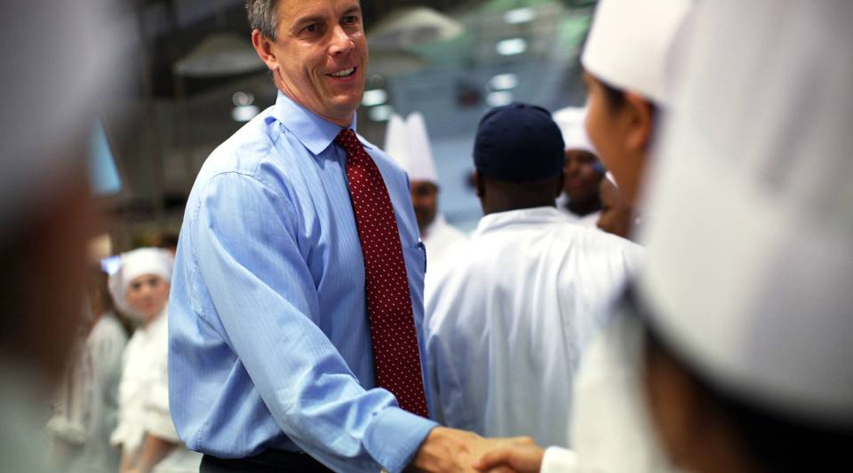 Then-Secretary of Education Arne Duncan meets with student chefs during a high school culinary contest in 2012.