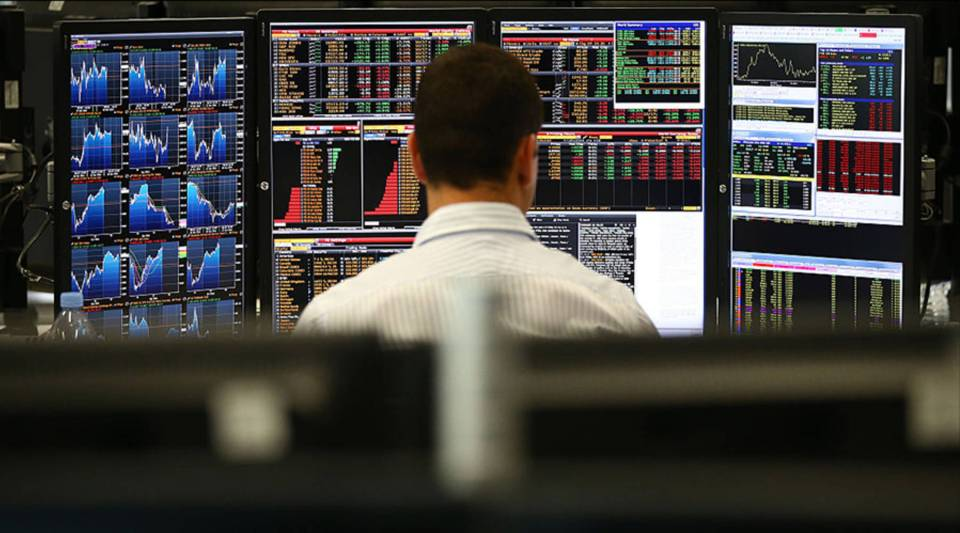An employee views trading screens at the offices of Panmure Gordon and Co. in 2014 in London.