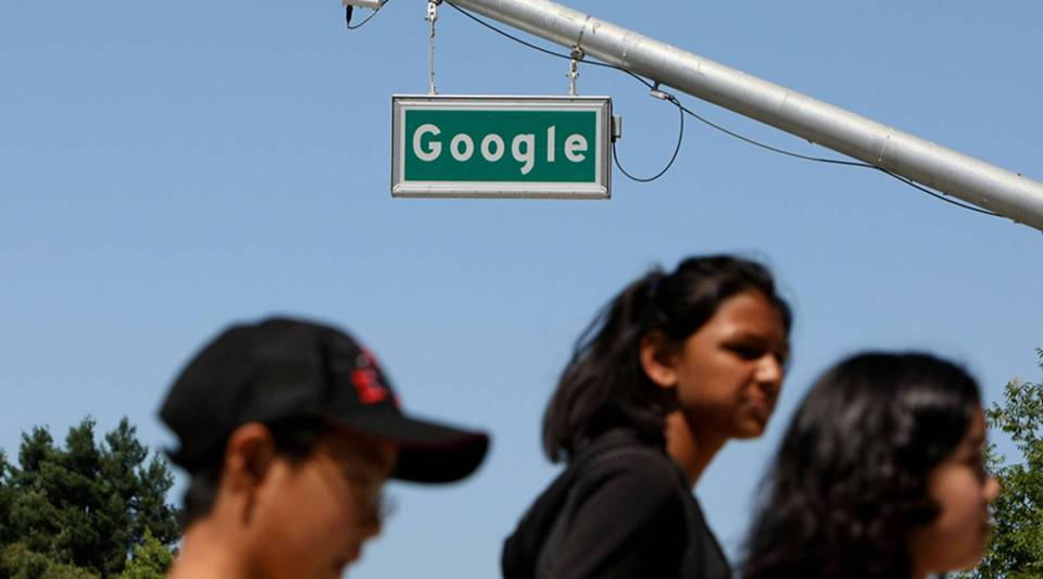 Pedestrians walk by a sign outside Google headquarters in Mountain View, California.