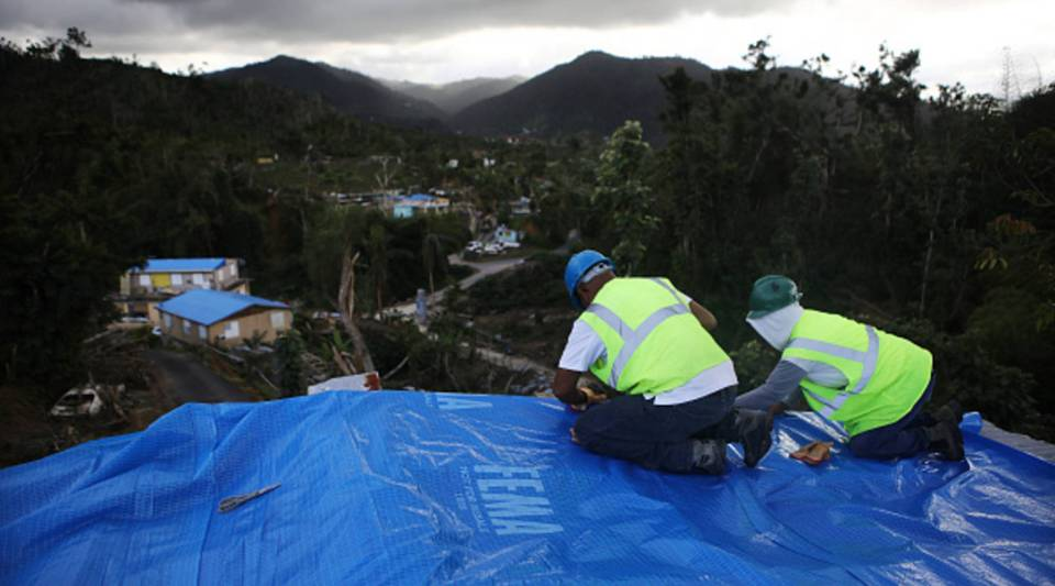 Contractors apply a FEMA tarp to a home damaged by Hurricane Maria and without electricity on Dec. 20, 2017 in Morovis, Puerto Rico.