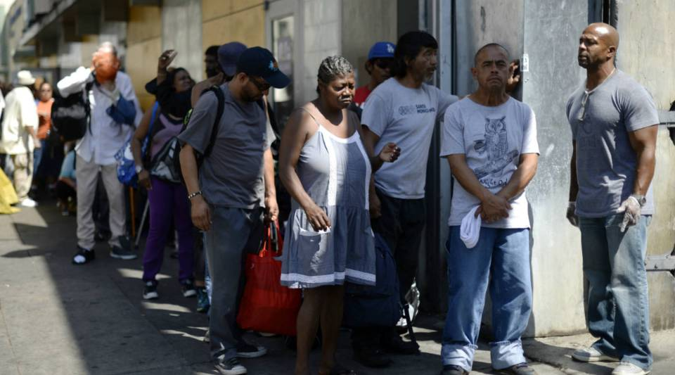 A homeless woman waits in line to receive groceries and clothing in the skid row section of Los Angeles, California.