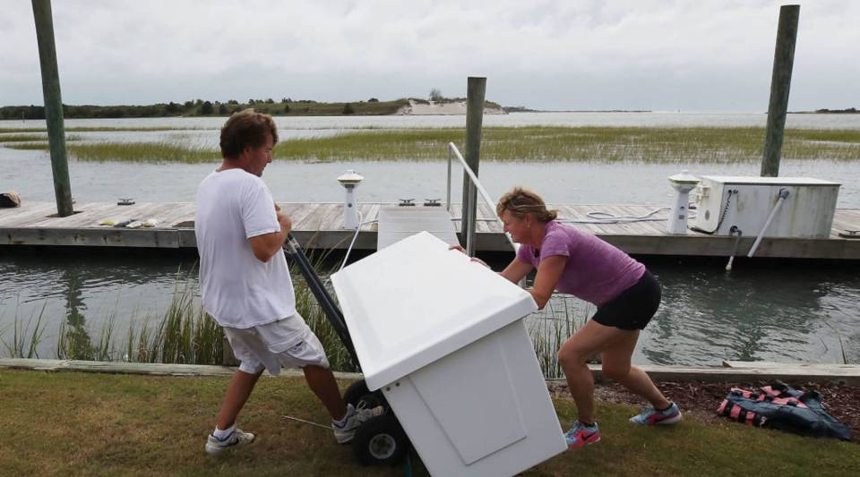 Mike Pollack and his wife, Meredith, move a dock box from their dock in Wilmington, North Carolina, Sept. 13 as Hurricane Florence approaches the area.