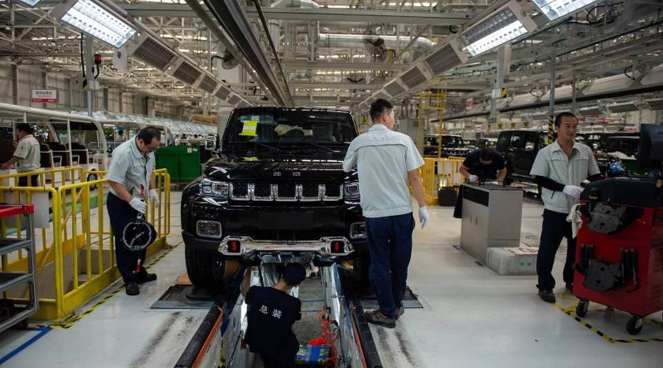 Employees work on an SUV production line at the Beijing Automotive Group Co. in Beijing in August.