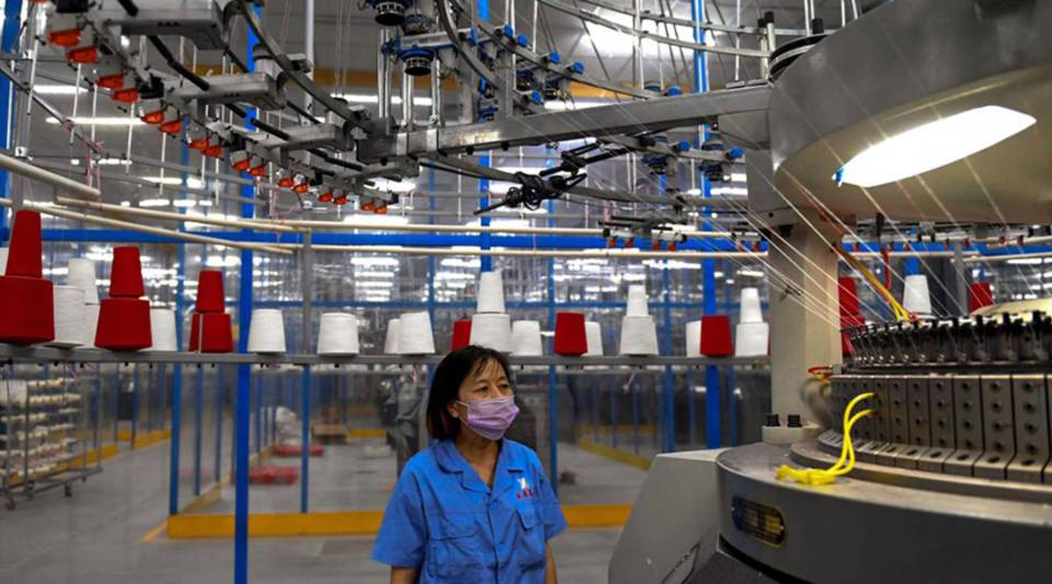 An employee monitors a circular weaving machine at a textile factory in Shangqiu in China's central Henan province in September.