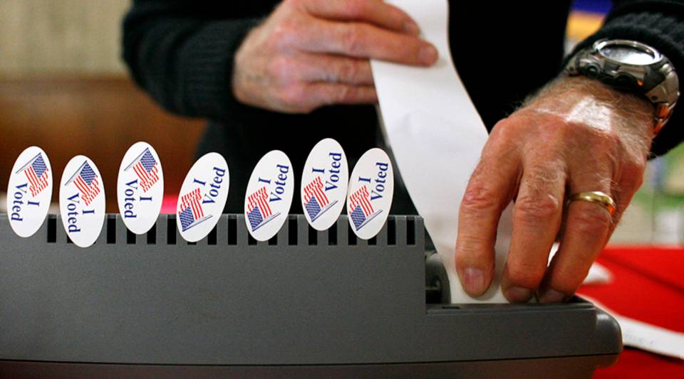 A pollster loads paper into a primary registration machine at the Travis County Courthouse in 2008 in Austin, Texas.