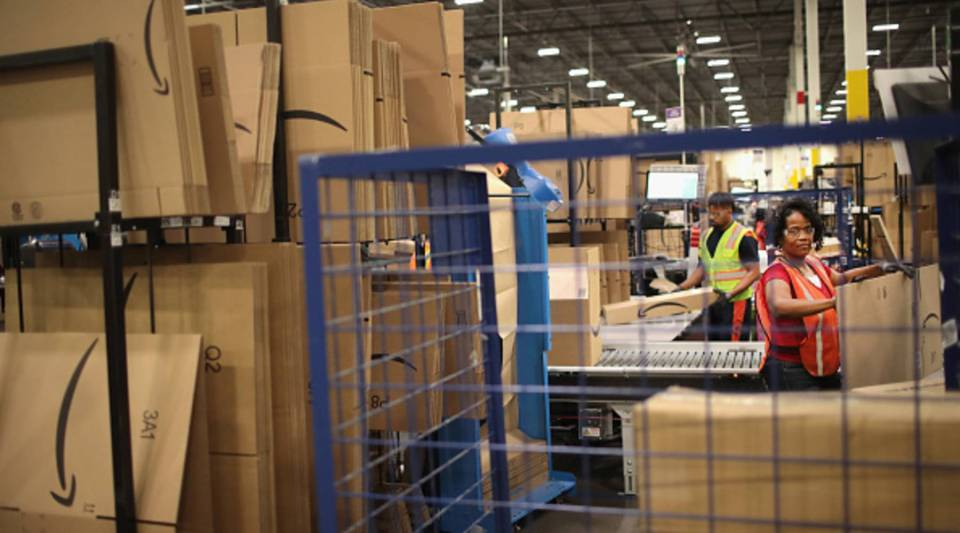 Workers pack and ship customer orders at the 750,000-square-foot Amazon fulfillment center on Aug. 1, 2017 in Romeoville, Illinois.