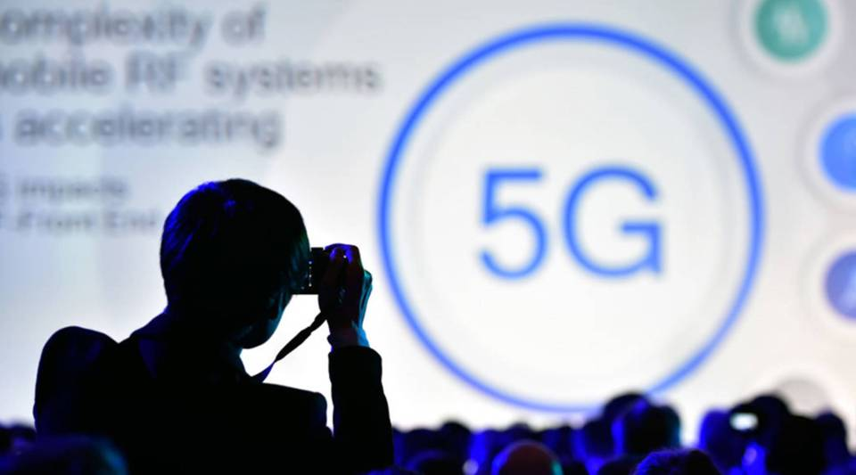 An attendee photographs a 5G logo display during a Qualcomm press event for CES 2018 at the Mandalay Bay Convention Center on January 8, 2018 in Las Vegas, Nevada.