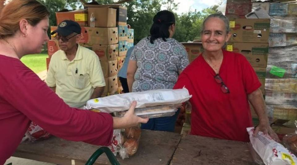 A volunteer at a food drop at the Church of God in Bithlo passes out fresh bread donated from Second Harvest Food Bank of Central Florida. Of the 93,000 meals they've provided so far this year, 80 percent of the food is considered nutritious.