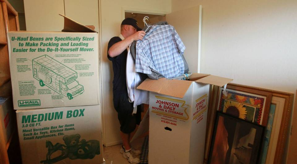 A worker packs a box with clothing while moving a family in Tiburon, Calif.