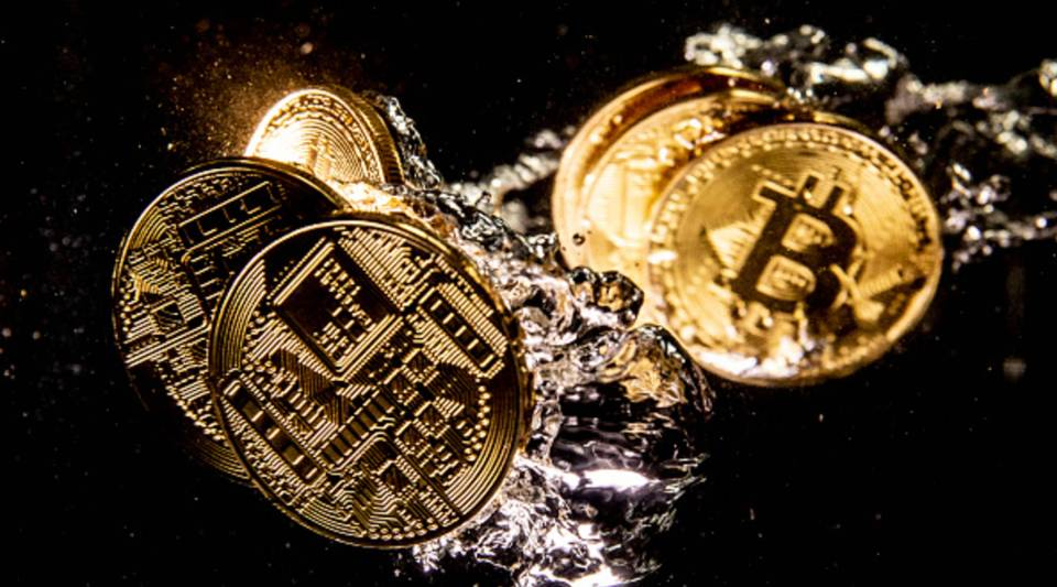 In this photo illustration a visual representation of the digital currency Bitcoin sinks into water.