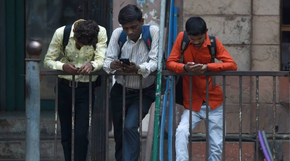 Indian men check their smartphones outside the Bombay Stock Exchange in Mumbai in October.