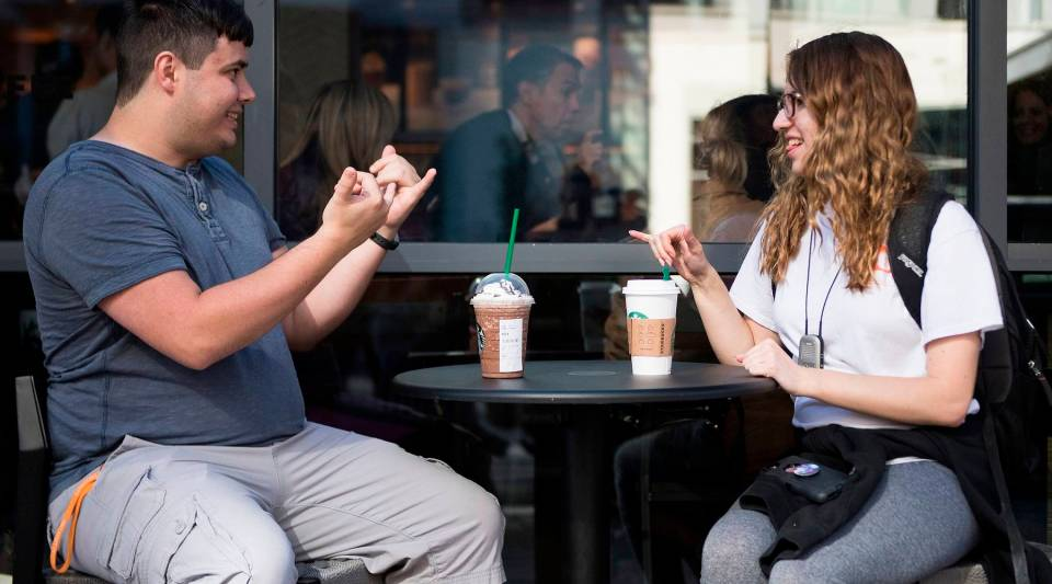 Sign language interpretation major student Nikolas Carapellatti (L) signs with deaf Gallaudet University student Rebecca Witzofsky outside the first Starbucks café staffed by employees who are partially or fully deaf and capable of communicating in American Sign Language in Washington, D.C., on Oct. 23, 2018.