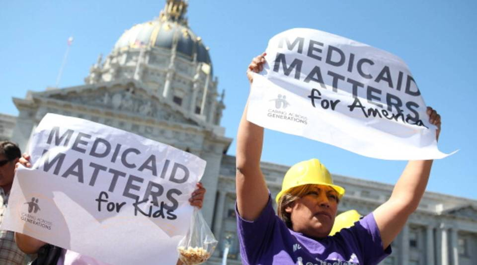 Protestors carry signs as they demonstrate against proposed cuts to Medical and Medicare outside San Francisco city hall on Sept. 21, 2011.