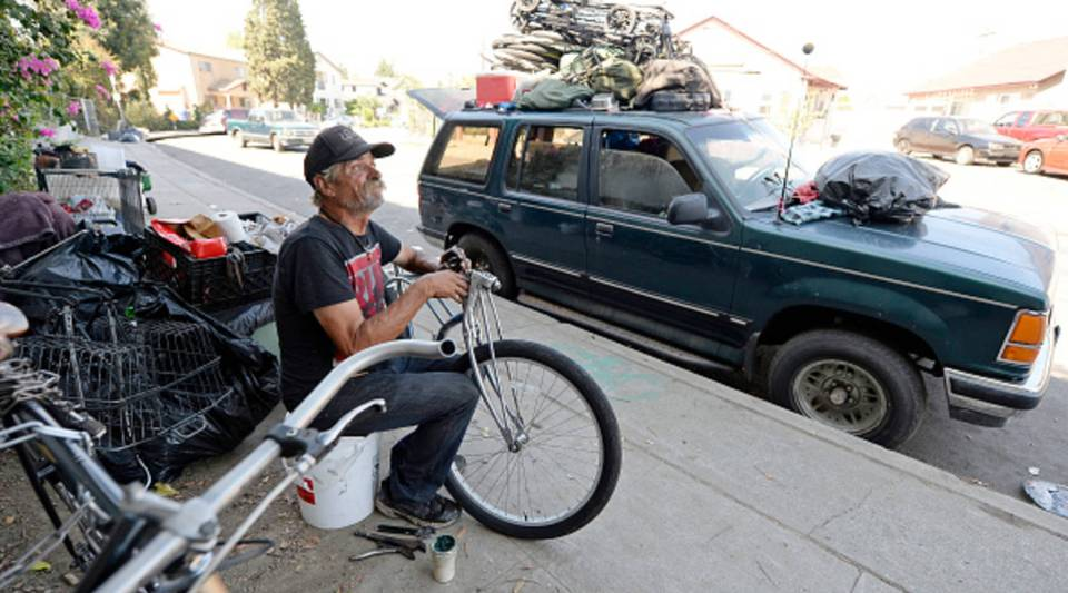 A homeless man for over 30 years, who lives inside his car, repairs a bicycle on Sept. 23, 2015 in Hollywood.