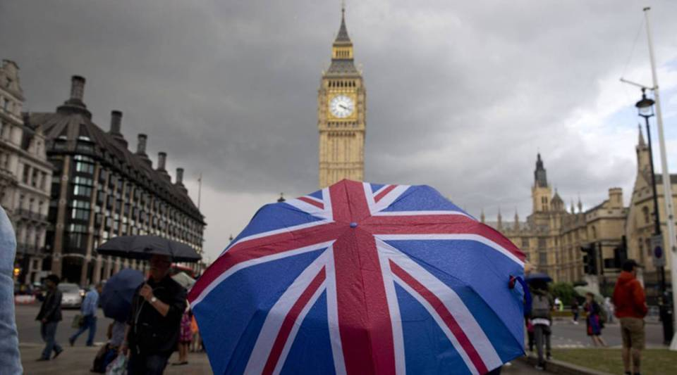 A pedestrian shelters beneath a Union flag-themed umbrella near Big Ben and the Elizabeth Tower at the Houses of Parliament in central London on June 25, 2016, following the pro-Brexit result of the U.K.'s EU referendum vote.