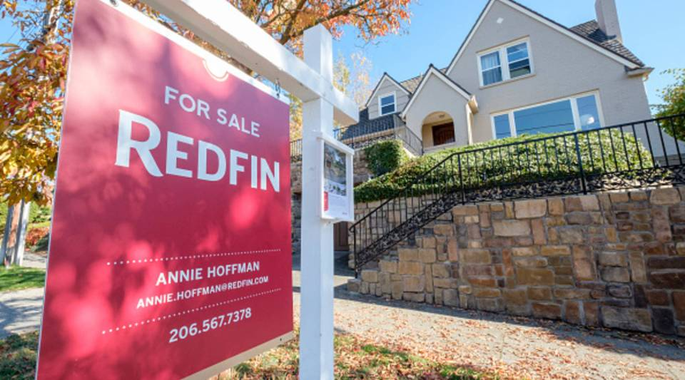 A Redfin real estate yard sign is pictured in front of a house for sale on Oct. 31, 2017 in Seattle, Washington.