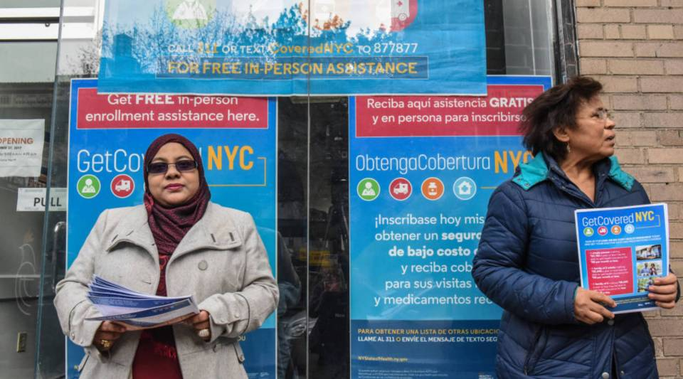 Workers pass out informational flyers in front of a new health care enrollment center in 2017 in the Queens borough of New York City.