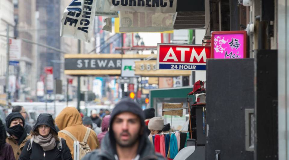 People walk past an ATM machine logo near Penn Station on January 8, 2018 in New York.