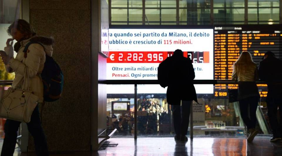 People stand in front of a 'debt clock' screen displaying the Italy's public debt at the Rome's Termini central station on February 15, 2018.
