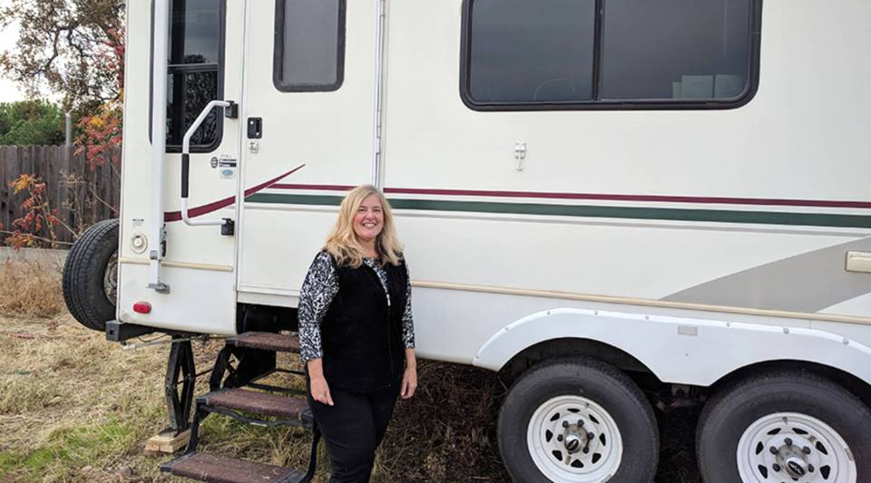 Kelley Conner stands outside the used RV she bought after the Camp Fire destroyed her home in Magalia, just north of Paradise, California.