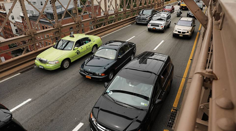 Cars drive through afternoon traffic on the Brooklyn Bridge on July 30, 2018 in New York City.