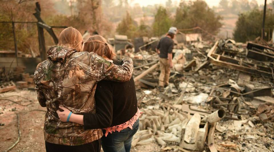 Kimberly Spainhower hugs her daughter Chloe, 13, while her husband Ryan Spainhower (R) searches through the ashes of their burned home in Paradise, California on November 18, 2018.