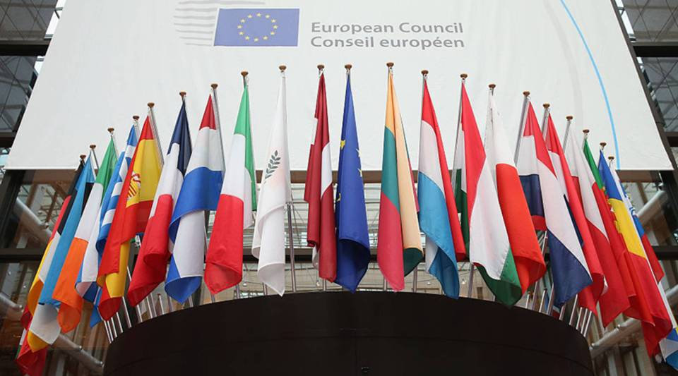Flags of the European Union member states hang inside the Council of the European Union's Lex building in Brussels.
