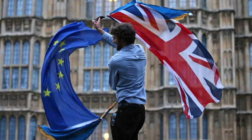 A man waves both a Union flag and a European flag together on College Green outside The Houses of Parliament at an anti-Brexit protest in central London on June 28, 2016.