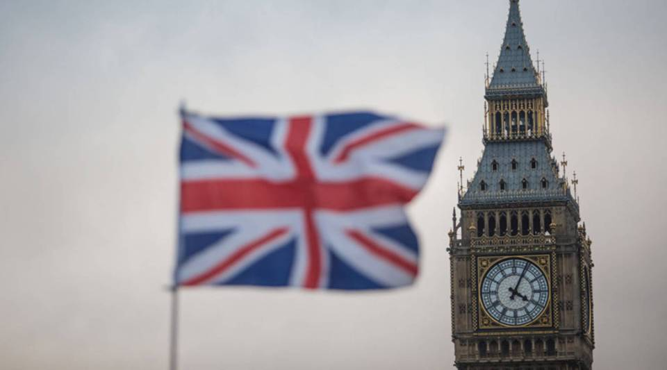 A Union Jack flag flutters in front of the Elizabeth Tower, commonly known as Big Ben, in London.