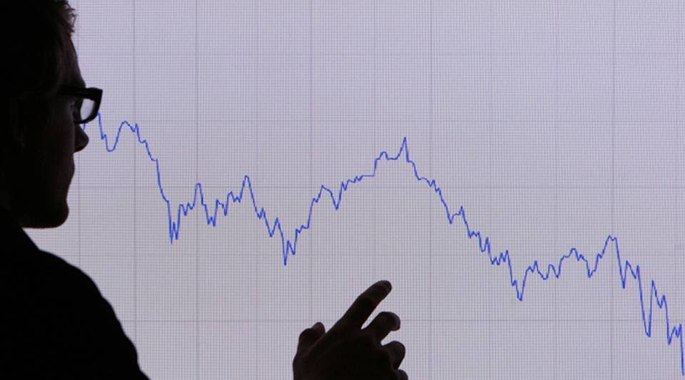 In this photo illustration, a man looks at a graph representing the 12-month decline of the FTSE 100 share index on Oct. 7, 2008, in London.