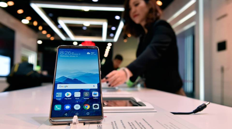 A Huawei representative prepares a Huawei smartphone for display during the 2018 International Consumer Eleectronics Show at the Las Vegas Convention Center.