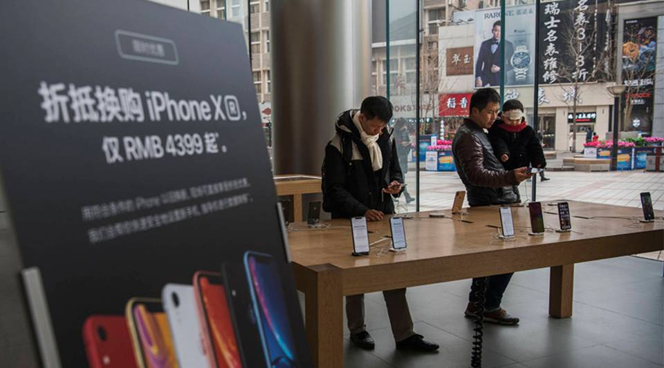 Customers look at iPhones on display at an Apple Store on this month in Beijing.