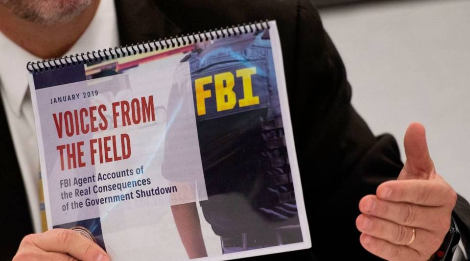 FBI Agents Association member Thomas O'Connor holds up an FBI report 'Voices From the Field' giving examples of how the government shutdown is undermining their work on drug and gang enforcement, security, and counter-terrorism, as he speaks during a press conference in Washington, DC, on January 22, 2019.