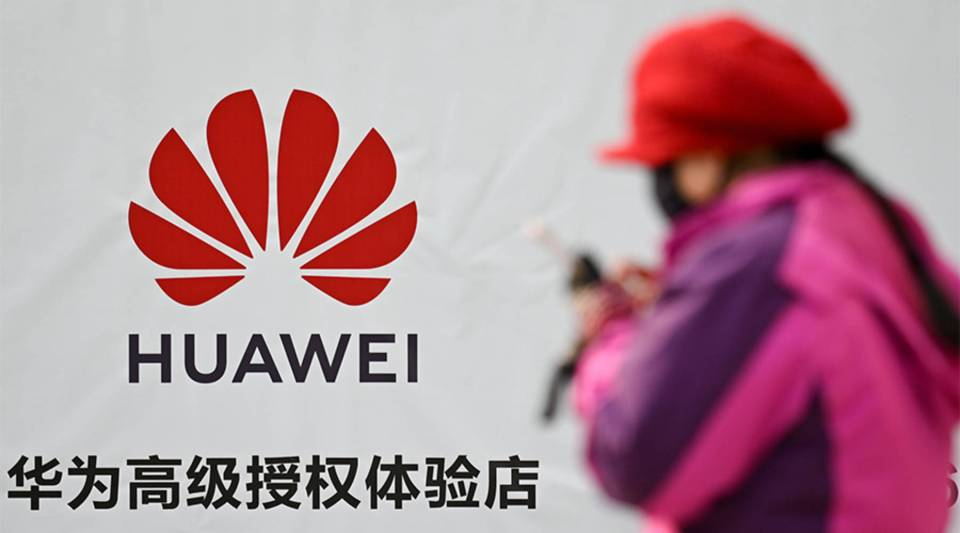 A woman uses her smartphone while walking past advertising outside a Huawei store in Beijing on Jan. 29, 2019.