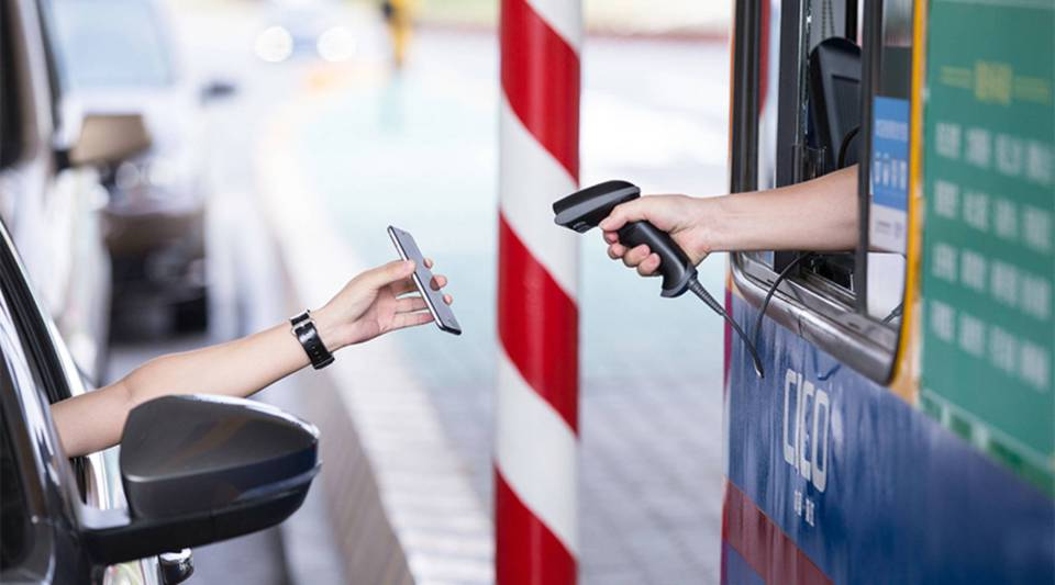 A driver pays a highway toll using mobile payment method Alipay in Zhejiang province.