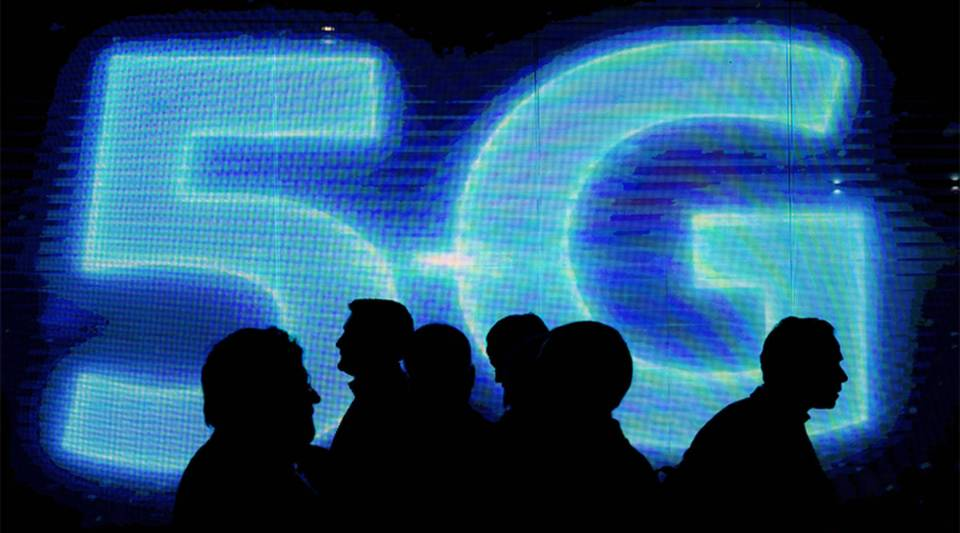 Visitors walk past a 5G logo during the Mobile World Congress in Barcelona, Spain.