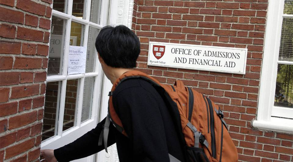 A prospective student enters the Harvard University Admissions Building in Cambridge, Massachusetts.