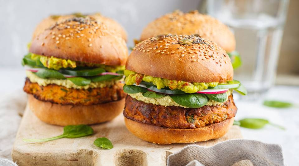 Healthy baked sweet potato burger with whole grain bun, guacamole, vegan mayonnaise and vegetables on a board.