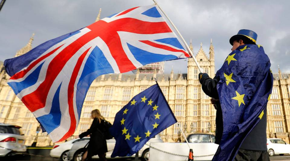 An anti-Brexit demonstrator waves a Union flag alongside a European Union flag outside the Houses of Parliament in London on March 28, 2018.